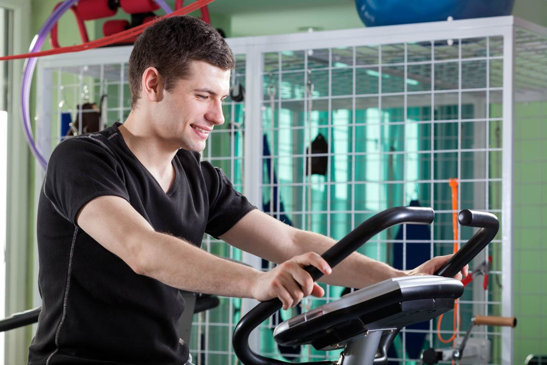 Man cycling on exercise bike at physiotherapy clinic